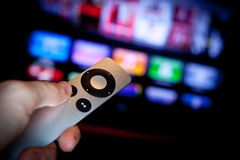 Apple TV In Action. Apple TV is a digital media receiver made and sold by Apple. It is a small form factor network appliance designed to play digital content Stock Photo