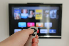 Apple TV. Aplle TV in action. hand holding the remote in front of the TV Royalty Free Stock Photography