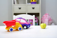Apple and two car toys on the table Royalty Free Stock Photography