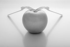 Apple with two forks Royalty Free Stock Images