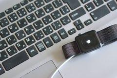 Apple-Uhr während OS-Aktualisierung mit unscharfem Laptop PC-Tastaturhintergrund lizenzfreies stockbild