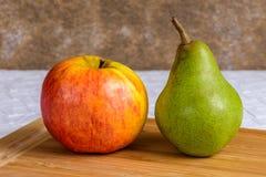 Apple und Birne auf einem Schneidebrett Stockbilder
