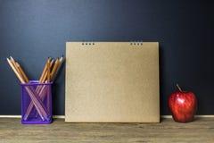 Apple und Bleistift auf hölzerner Tabelle mit leerem Brown-Papier auf Schwarzem Lizenzfreie Stockfotografie
