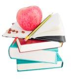 Apple und Pillen auf großem Stapel der Bücher Stockbilder