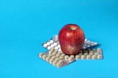 Apple und Pillen getrennt auf Blau Lizenzfreie Stockfotografie