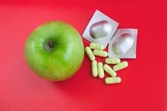 Apple und Tabletten über hellem rotem Hintergrund Lizenzfreie Stockfotografie