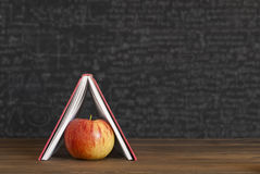 Apple under books, house. Apple under books blackboard - chalk Royalty Free Stock Photo