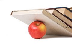 Apple under a pile of books Stock Image