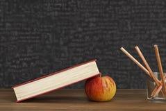 Apple unter Büchern mit Bleistiften und leerer Tafel - zurück zu Schule Lizenzfreie Stockfotografie