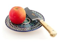 Apple and Uzbek knife on a Rishtan style plate. Isolated photo of Central Asian (Uzbek) desert plate with apple and traditional knife Stock Photography
