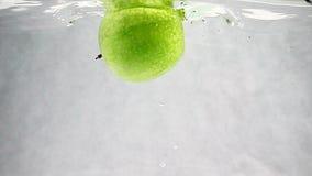 Apple verde cae en el agua lentamente Frutas aisladas en un fondo blanco almacen de metraje de vídeo
