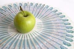 Apple verde en billetes de banco imagenes de archivo