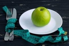 Apple verde en la placa con la cinta métrica en el fondo de madera Imágenes de archivo libres de regalías