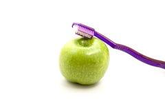 Apple verde fresco con el cepillo de dientes Fotos de archivo libres de regalías