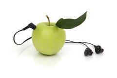 Apple verde fresco con los auriculares Fotos de archivo