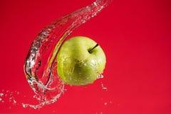 Apple verde no fundo vermelho Imagens de Stock Royalty Free