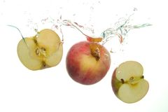 Apple vermelho e e duas fatias do aple espirram na água no fundo branco fotografia de stock royalty free