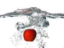 Apple vermelho que cai na água fresca isolada em Backgro branco imagens de stock