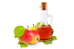 Apple vinegar. Apple cider vinegar cruet and ripe apples with green leaves on a white background royalty free stock photo