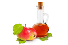 Apple vinegar. Apple cider vinegar cruet and ripe apples with green leaves on a white background stock images