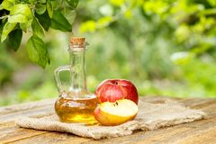 Apple vinegar in glass bottle and fresh red apples on wooden boa. Apple vinegar in glass bottle with cork and fresh red apples on sackcloth and old wooden boards stock photography