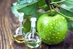 Apple vinegar in glass jar with ripe green fruit. Bottle of apple organic vinegar on wooden background. Healthy organic food. Apple vinegar in glass jar with Royalty Free Stock Photography