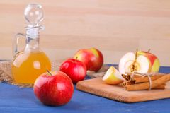 Apple vinegar with ripe apples on a blue wooden background royalty free stock photos