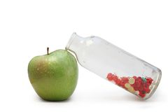 Apple and vitamins. Photo of a green apple and bottle with vitamins Stock Images