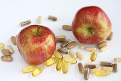 Apple Vitamins. Close up of fresh red apples with different vitamin pills against white background stock photo