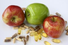 Apple Vitamins. Close up of fresh green and red apples with different vitamin pills against white background royalty free stock photos