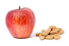 Apple and vitamins in tablets. Stock Image