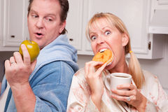 Apple vs. Donut Healthy Eating Decision. Couple in Kitchen Eating Donut and Coffee or Healthy Fruit Stock Images