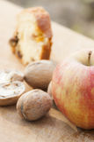 Apple, walnuts and cake. An apple in foreground, then some walnuts and then, a slice of homemade cake in the background. All of them are lighted by natural Stock Image