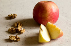 Apple and walnuts on the table Royalty Free Stock Photography