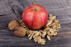 Apple and walnuts on wooden background. Red apple and walnuts on wooden background Stock Photography