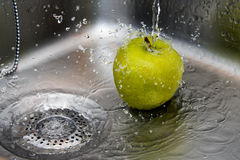 Apple wash. Apple getting wash under tap water Stock Images