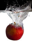 Apple in water. One red apple falls in water stock photography