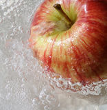 Apple in water. Red healthy apple in the water (close-up background Royalty Free Stock Photo