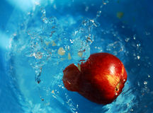 Apple in water. Apple in blue water broken, with apple pulp rushed from the apple in the water Stock Photos