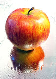 Apple. In water droplets lying on the mirror Royalty Free Stock Image