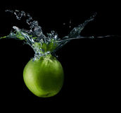 Apple with water splash isolated. Freshness, shine, vegetarian royalty free stock image