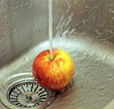 Apple and water splashes in a sink Stock Image