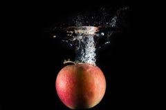 Apple in water wordt gelaten vallen dat royalty-vrije stock afbeelding