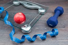 Apple on weighing scale with measure tape royalty free stock image