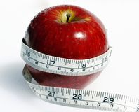 Apple weight watcher. A gorgeous red apple with a tape measure wrapped around it, signifying healthy eating and eating responsibly royalty free stock images