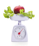 Apple on weights. Bright red apple and salad on weights isolated on white Stock Image