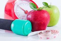 Apple and weights with measuring tape. Dumbells with measuring tape and apples royalty free stock photography