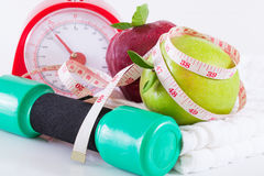 Apple and weights with measuring tape. Dumbells with measuring tape and apples stock photography