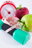 Apple and weights with measuring tape. Dumbells with measuring tape and apples stock photos