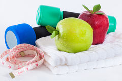 Apple and weights with measuring tape Royalty Free Stock Photo